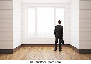 Businessman in unfurnished room - Businessman standing in...