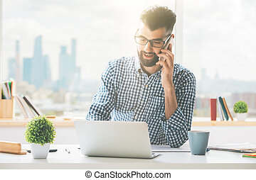 Handsome man on phone using laptop