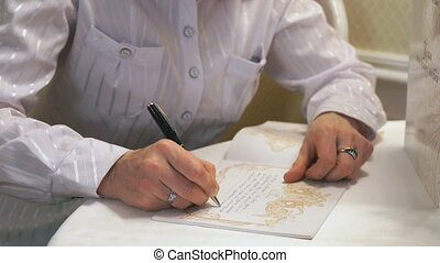 Female hand writing greeting text in book.Close up - Female...