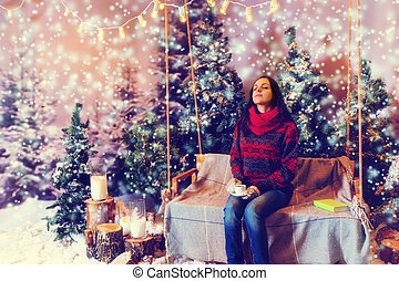 Young dreaming woman sitting on a swing with a blanket under...