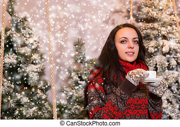 Portrait of smiling young woman sitting under the...