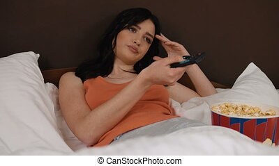 Young brunette woman watching TV and eating popcorn in her bed.