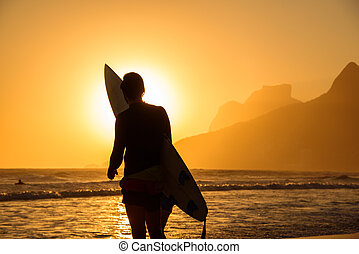 Silhouette of one surfer holding his surfboard on the...