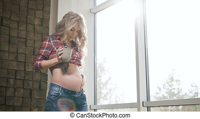 Beautiful pregnant woman dressed in plaid shirt and blue jeans standing near the window and touching her belly lovingly. Future mother is happy and smiling