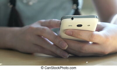 Schoolgirl sitting at a desk holds a mobile phone - The...