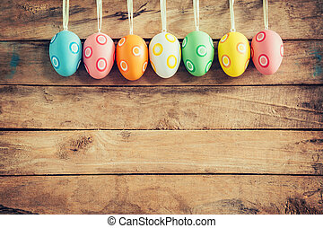 Colorful easter eggs hanging on rustic wooden background...