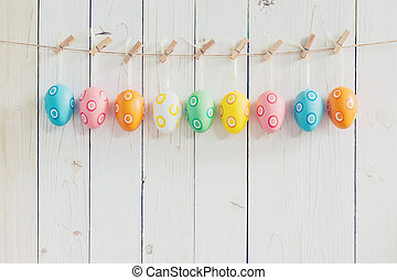 Colorful easter eggs hanging on rustic wooden white...