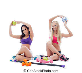 Two smiling young female athletes posing in studio
