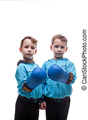Two serious twins posing in boxing gloves, isolated on white