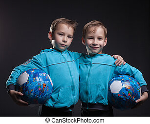 Portrait of smiling twin boys posing with balls, close-up