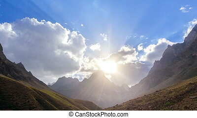 Peaks in the clouds at sunset. Pamir, Tajikistan