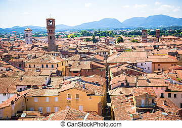 Beautiful view of ancient old buildings with red roofs background mountains in Lucca, Italy