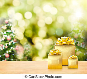 Golden presents on wood table top with christmas tree...