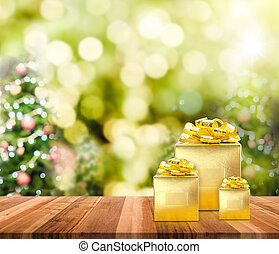 Golden presents on wood plank table top with christmas tree...