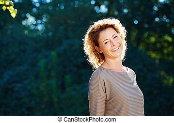 Happy older woman standing in tranquil park