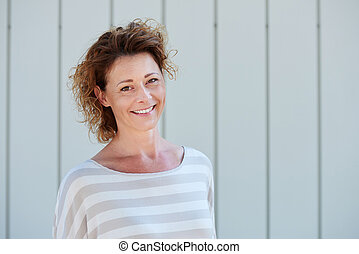 Happy older woman smiling against white wall