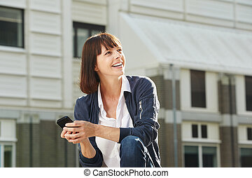 Happy woman sitting outside in city with smart phone -...