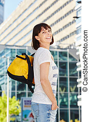 Happy older woman carrying duffel bag in city - Portrait of...