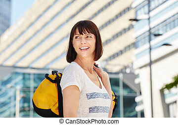 smiling older traveler carrying duffel bag in city -...