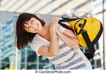 happy traveler carrying duffel bag over shoulder - Portrait...