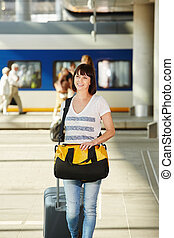 Female traveler with duffel bag and suitcase at train...