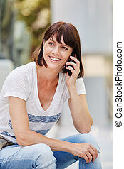 Older woman sitting outside talking on mobile phone in city...