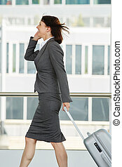 Traveling business woman walking and talking on cell phone