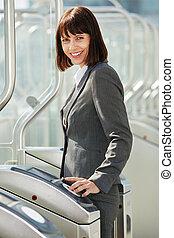 professional business woman walking through platform barrier...