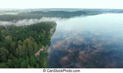 flying above fog over lake early in the morning - fog over...