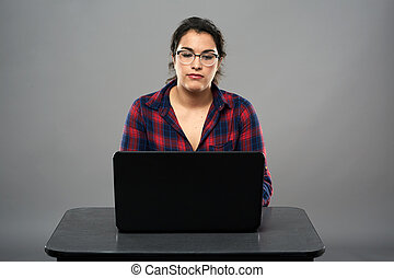 Latino businesswoman with laptop on desk