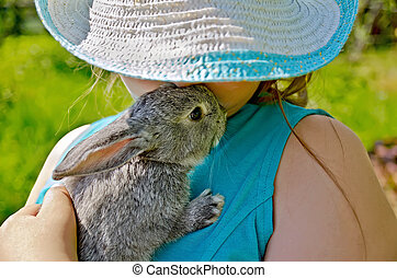 Rabbit gray on hands of girl in hat - Little gray rabbit in...