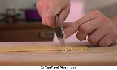 Man cutting homemade pasta with a knife. 4K steadicam close...