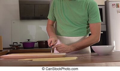 Man in green cutting homemade pasta with a knife. Amateur...