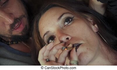 Young Woman Smoking Marijuana Cigarette With Boyfriend At...