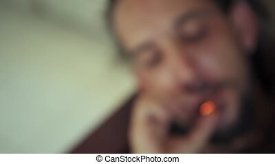Young Man And Woman Smoking Marijuana Cigarette At Home -...
