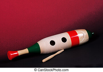 Guiro Goard on Red - A guiro gourd percussion instrument...