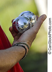 Hand of man holding petanque ball or boule, France