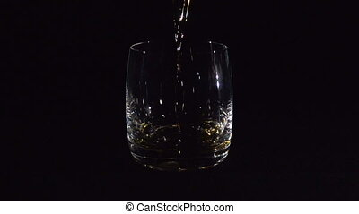 Whiskey Pouring into Glass on Black - Whiskey pouring into...