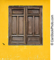 Brown wooden window on yellow wall in Hoi An, Vietnam.