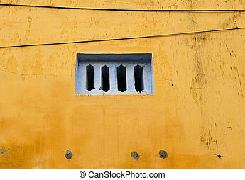 Blue window on yellow wall in Hoi An, Vietnam.