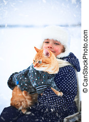 Little girl holds a red cat in her hands.