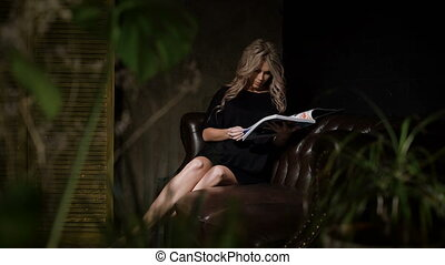 Pregnant woman in beautiful black dress sitting in the dark room on the big brown leather sofa with the flowers foreground and turning pages of magazine