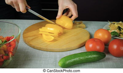 Girl with a knife cuts ripe yellow pepper - The girl with a...
