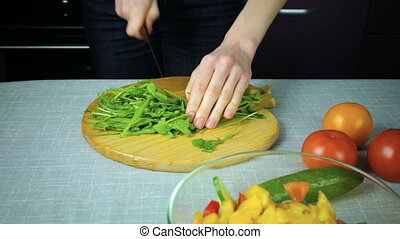 Chef slices arugula on a wooden board - Girl cook slices...