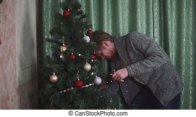 man is decorating a Christmas tree
