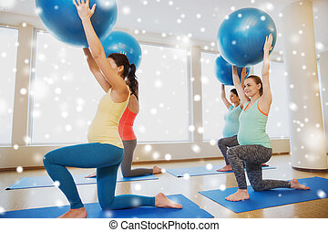 happy pregnant women with exercise balls in gym