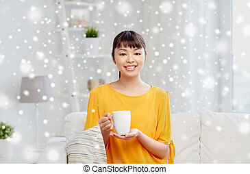 happy asian woman drinking from tea cup - people, drinks and...