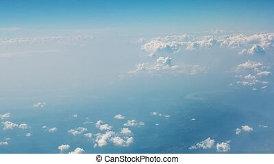 Blue sky with white clouds. View of clouds and land from an airplane window