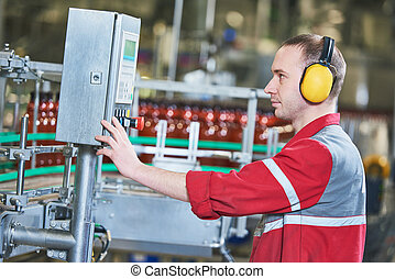Factory worker operating conveyor with beer beverage bottles...