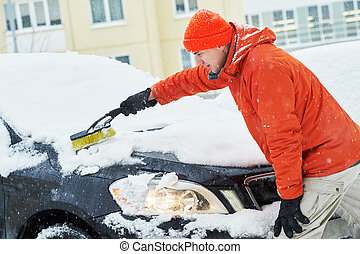 man cleaning car from snow